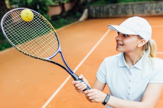 열린 테니스 코트에서 귀여운 얼굴을 한 아름다운 젊은 여자가 테니스를 치고 있습니다. 놀 준비가 되었습니다.