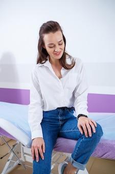 ジーンズと白いシャツを着た美しい少女、医療センターの医師の診察を受けた患者
