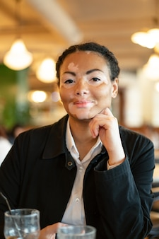 A beautiful young girl of african ethnicity with vitiligo sitting in a restaurant