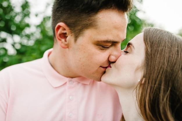 Красивая молодая девушка и ее муж целуются с закрытыми глазами на фоне природы