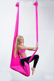 Beautiful young girl antigravity yoga on a pink silk hammock while doing.