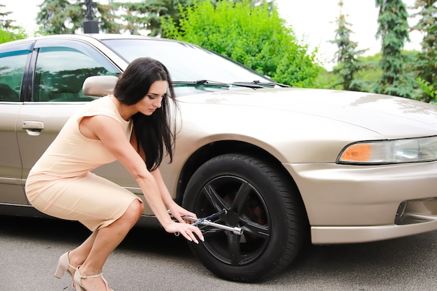 Beautiful young girl on a background of a car and a key for spinning wheels