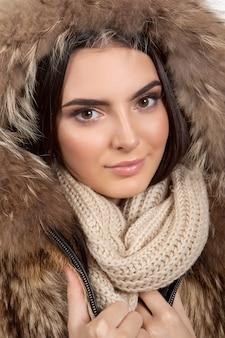 美しい少女は、冬のクリスマスの服、毛皮のコート、目を閉じてスカーフを浴びます。