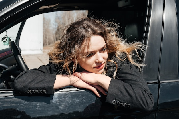 Beautiful, young girl in a black car. the girl sits behind the wheel and looks out of the window.