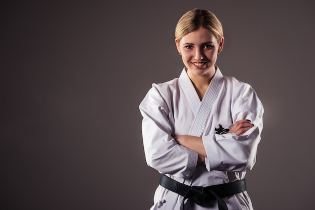 Beautiful young girl blonde karate sportswoman in a kimono makes a position to start workout.