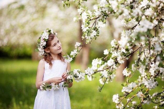 Beautiful young girl in blue dress in the garden with blosoming  apple trees. cute girl  holding apple-tree branch