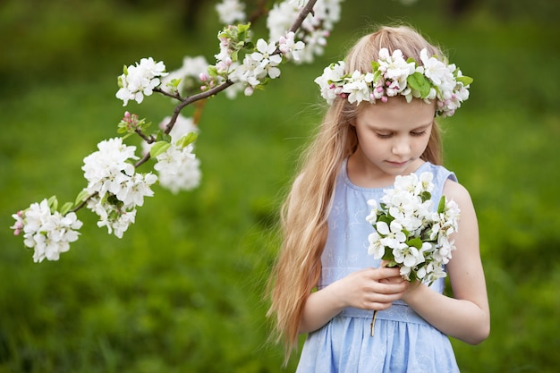 Beautiful young girl in blue dress in the garden with blosoming  apple trees. cute girl  holding a bouquet of flowers