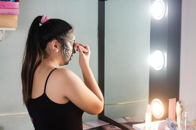Beautiful young girl blurring her halloween makeup in her room.