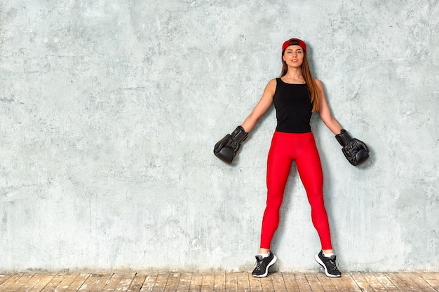 Beautiful young girl boxing gloves near the wall. close-up copy space.
