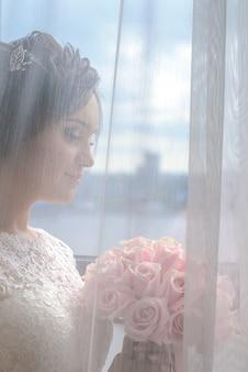 白いドレスを着た美しい少女の花嫁は、窓の透明なカーテンの後ろに立っています