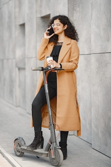 Beautiful young girl in a brown coat. woman riding an electric scooter.
