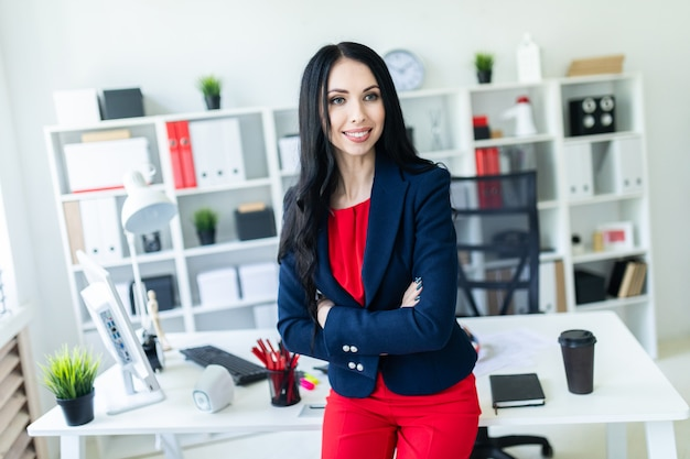 Beautiful young girl in a business suit is standing in the office, leaning on a table.