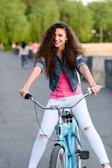 Beautiful young girl in casual clothes resting and cycling in the summer in the city along the embankment