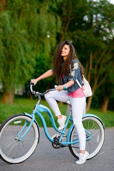 Beautiful young girl in casual clothes rides a city bike in summer