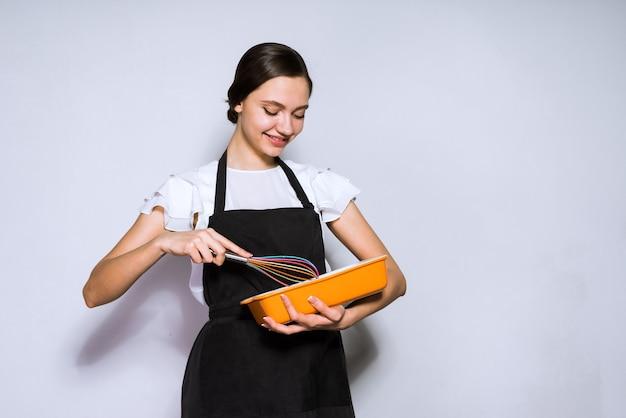 おいしいパイを準備する黒いエプロンの美しい若い女の子のシェフ