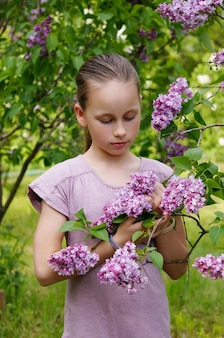 A beautiful young  girl child in the garden smelling lilac