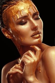 Красивый крупный план молодой девушки с блестящей кожей и золотым цветом. темные волосы, профессиональный макияж, чистая кожа.