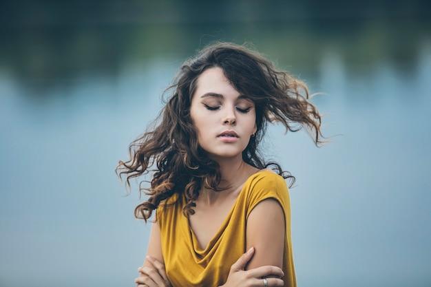 明るいドレスの水の背景に美しい若い女の子のクローズアップの肖像画