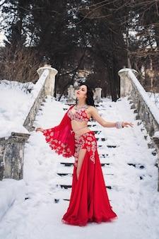 Красивая молодая девушка танцует танец живота в красном платье зимой в парке на снегу.