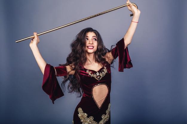 Красивая молодая девушка танцует с саиди танца живота тростью.