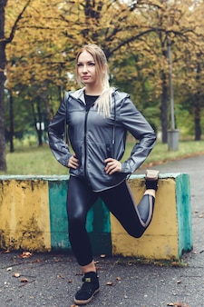 Beautiful young girl doing sports exercises in a park at rainy weather.