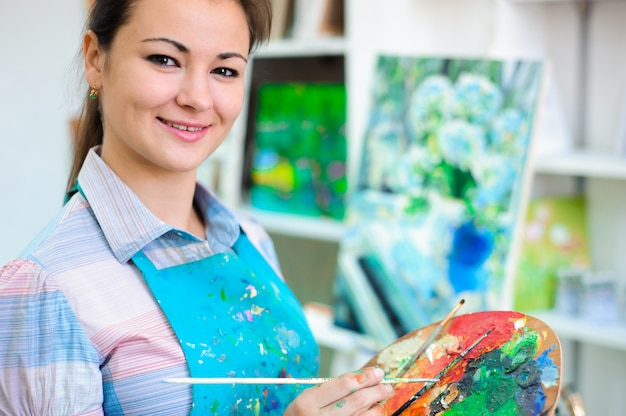 美しい少女は、アートレッスンで絵の具を描画します