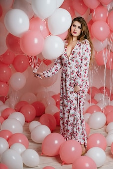 Beautiful young girl in a dress among a lot of pink balls.
