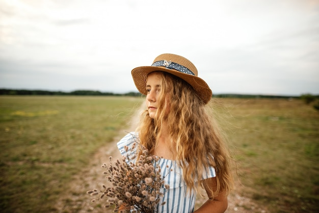 Beautiful young girl in a dress with blonde hair and a hat walks across the meadow