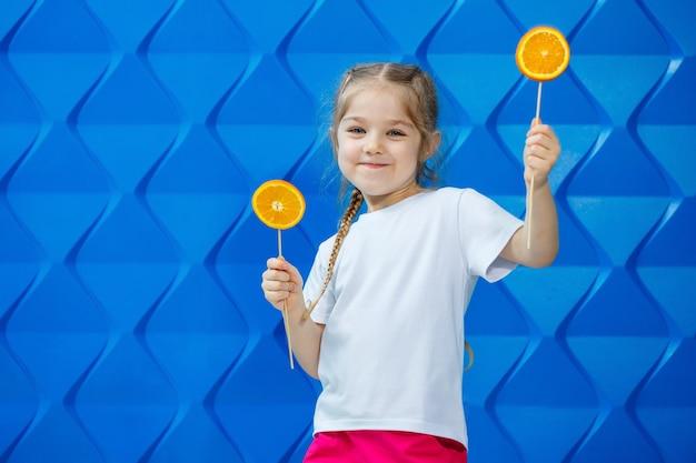 白いtシャツを着た美しい少女は、オレンジ色の半分を手に持って微笑んでいます。オレンジ色の果物、彼女はオレンジを噛み、好きです。