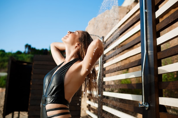 Beautiful young  girl dressed in swimwear taking a shower on beach