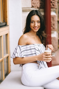 Beautiful young girl drinking coffee in the city