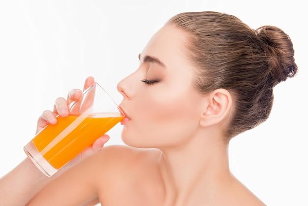Красивая молодая девушка пьет апельсиновый сок