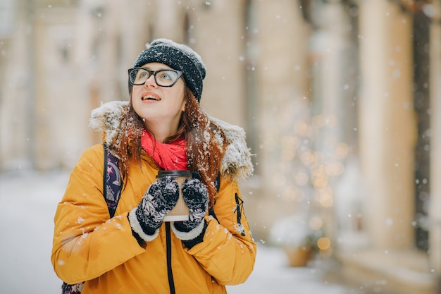 Beautiful young girl drinks coffee looking around in snowy winter city