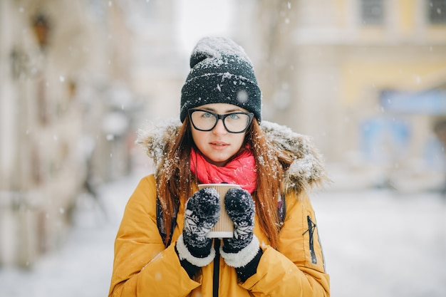 Beautiful young girl drinks coffee in snowy winter city