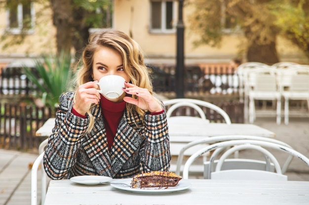 Beautiful young girl drinks coffee at a table of small street cafe.