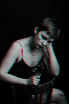 Beautiful young girl drinks red wine and is sad. black and white with glitch effect