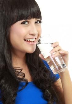Красивая молодая девушка пьет воду из стекла