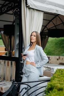 Beautiful young girl drinks wine on the veranda of a beautiful house. holiday.