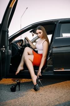 Красивая молодая девушка за рулем автомобиля вечером на закате на пустой парковке