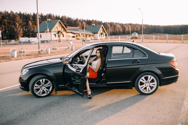 空の駐車場で夕日の太陽の下で夕方に車を運転する美しい少女