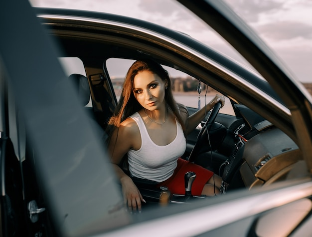 Beautiful young girl driving a car in the evening in the sunset sun on an empty parking lot
