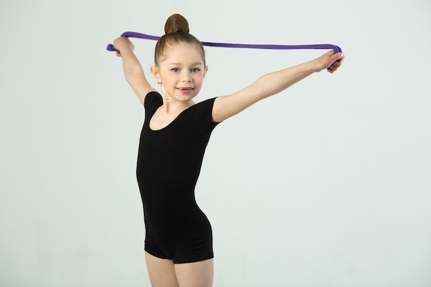 Beautiful young girl engaged in gymnastics on a white wall in a black suit
