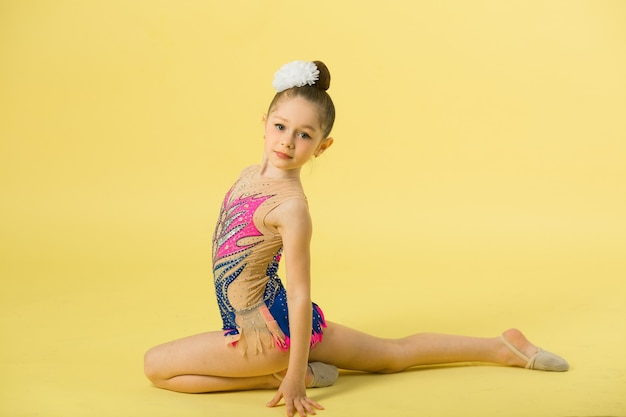 Beautiful young girl engaged in gymnastics on a yellow wall