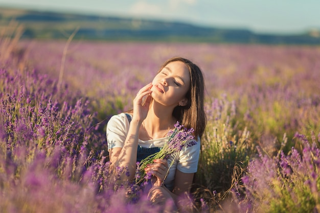 Beautiful young girl enjoying the sunlight in a lavender field