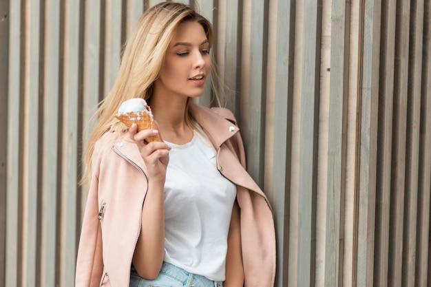 Beautiful young girl in fashionable clothes is holding ice cream near a wooden wall on a summer day