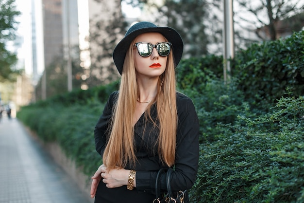 Beautiful young girl in a fashionable hat and sunglasses
