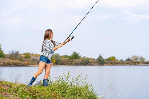 Beautiful young girl fishes on the lake.