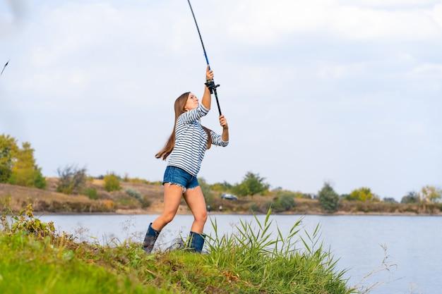 美しい少女は湖で魚します。