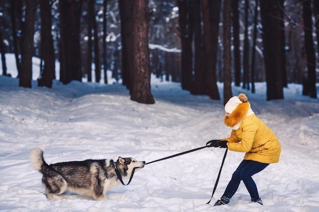 Красивая молодая девушка смешно играет со своей собакой зимой в парке. собака и девочка волочатся на поводке. концепция счастливого зимнего отдыха