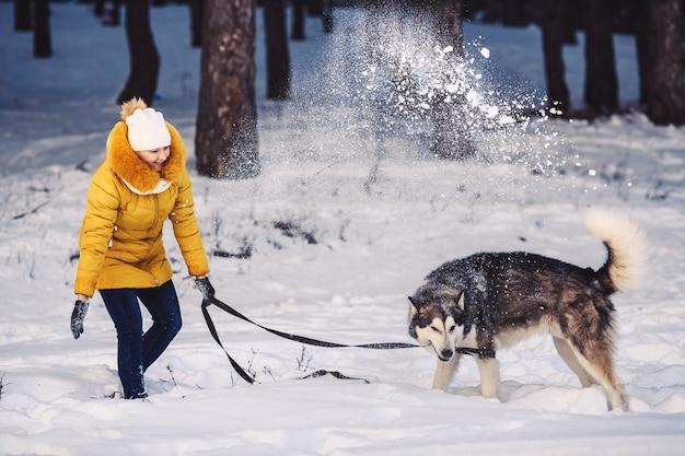 Красивая молодая девушка смешно играет со своей собакой зимой в парке. женщина смешно бросает снег в собаку. концепция счастливого зимнего отдыха